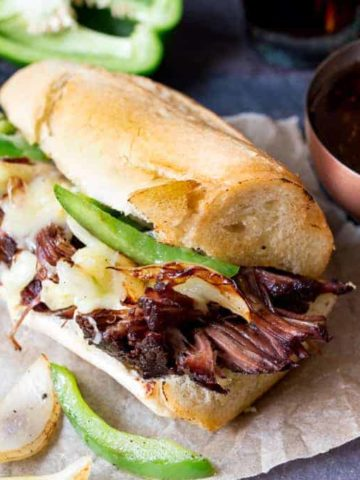Slow-cooked brisket dip sandwich with peppers, onion and cheddar. Flavour packed and delicious!