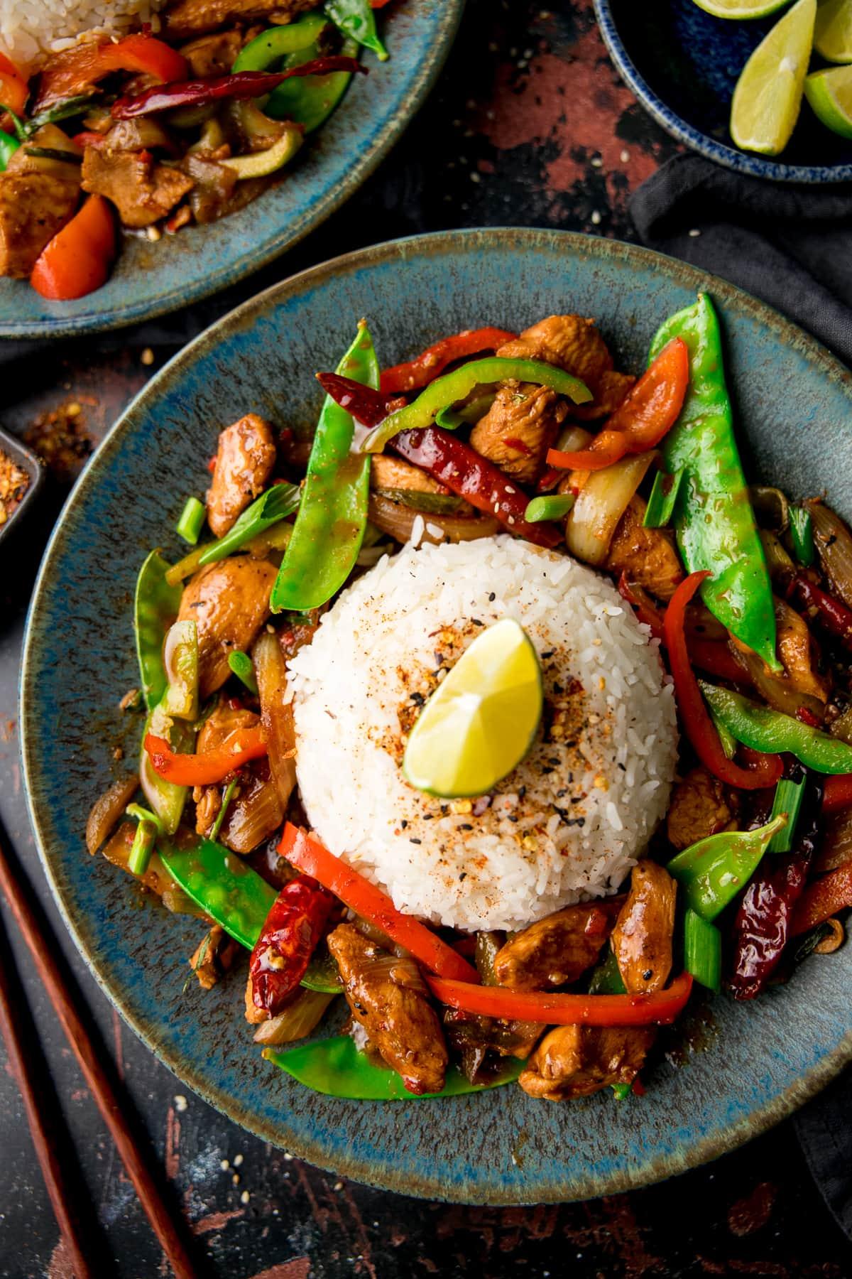 Firecracker chicken stir fry surrounding a mound of rice on a blue plate