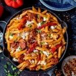 Overhead of penne arrabiata pasta in a pan on dark background