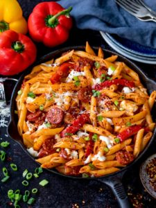 Penne arrabiata pasta in a pan on dark background with peppers and spring onions scattered around pan