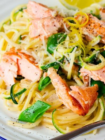 White plate topped with spaghetti, zoodles, sugarsnap peas, flaked salmon and lemon zest