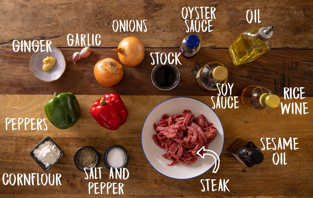 Ingredients for black pepper beef stir fry on a wooden table.