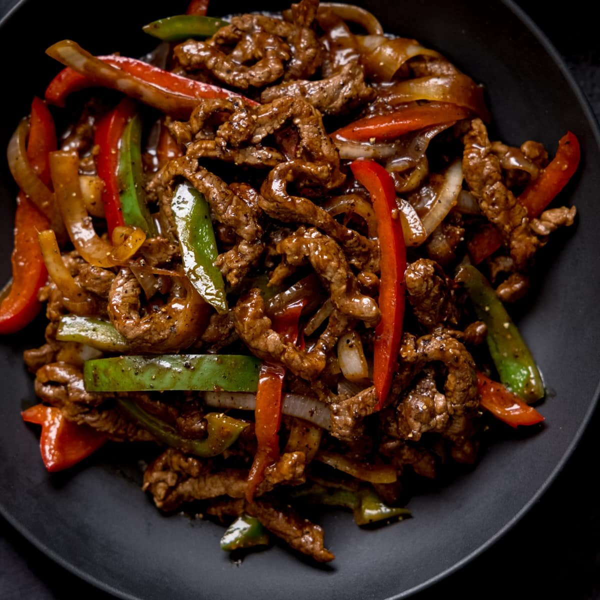 Black pepper beef stir fry with red and green peppers in a black bowl