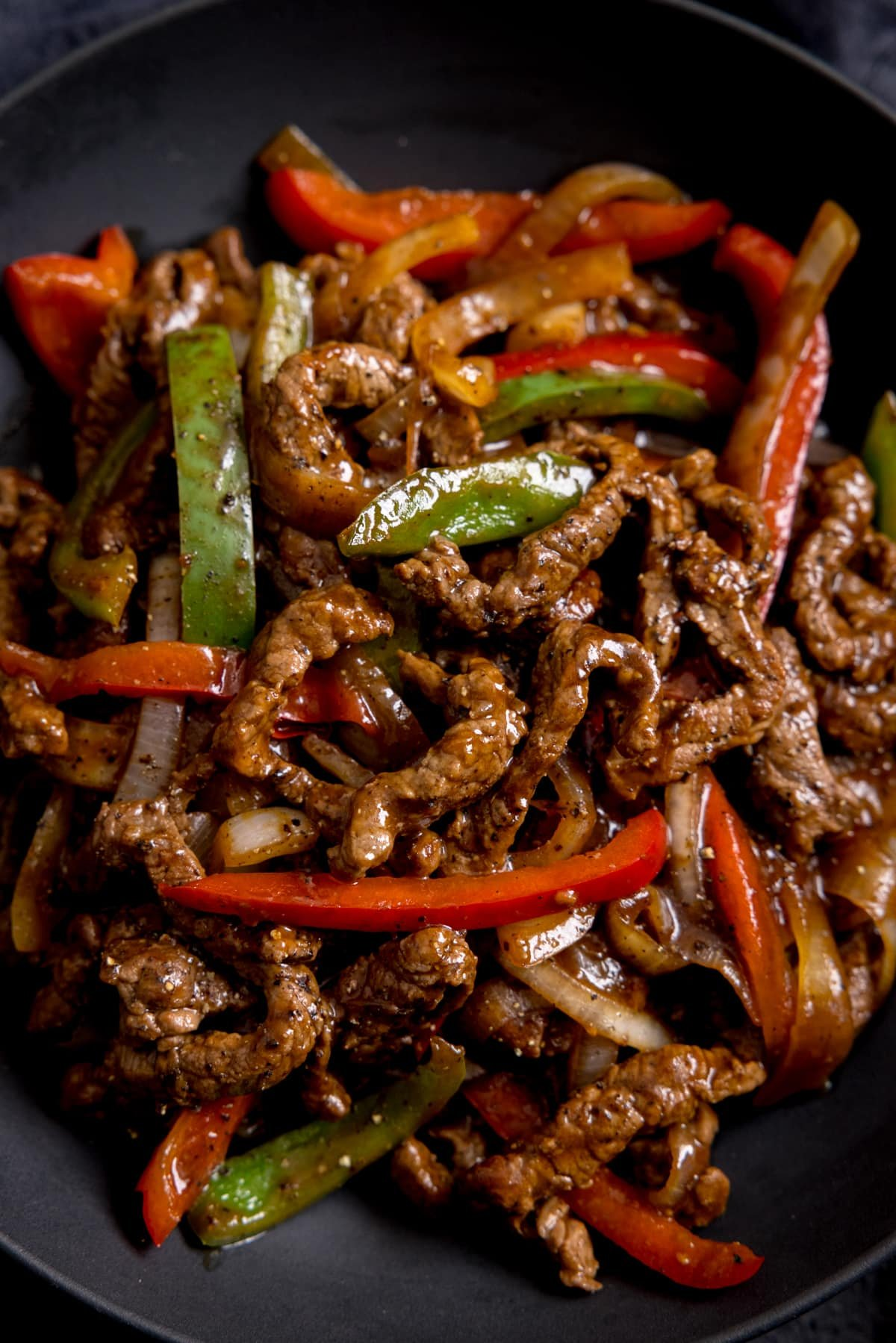 Close up of black pepper beef stir fry with red and green peppers in a bowl