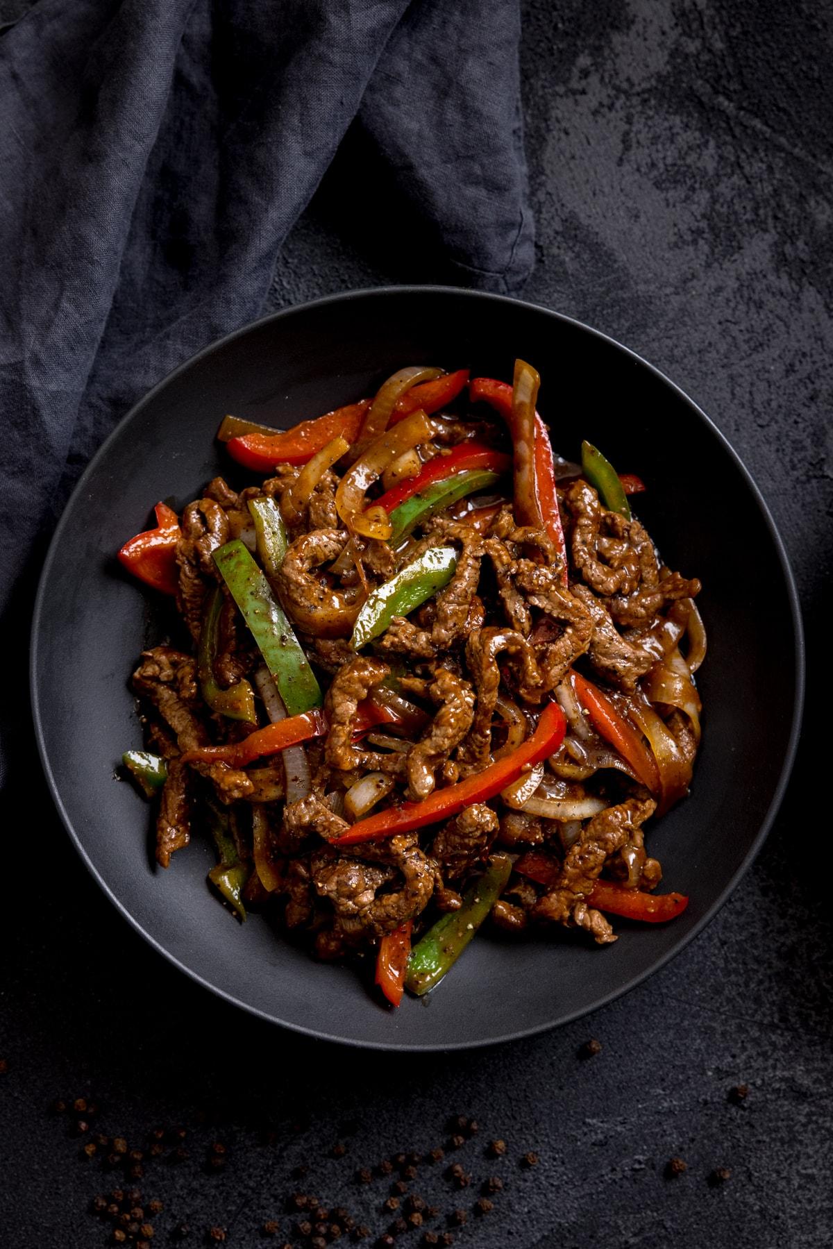 Black pepper beef stir fry in a black bowl on a dark background.