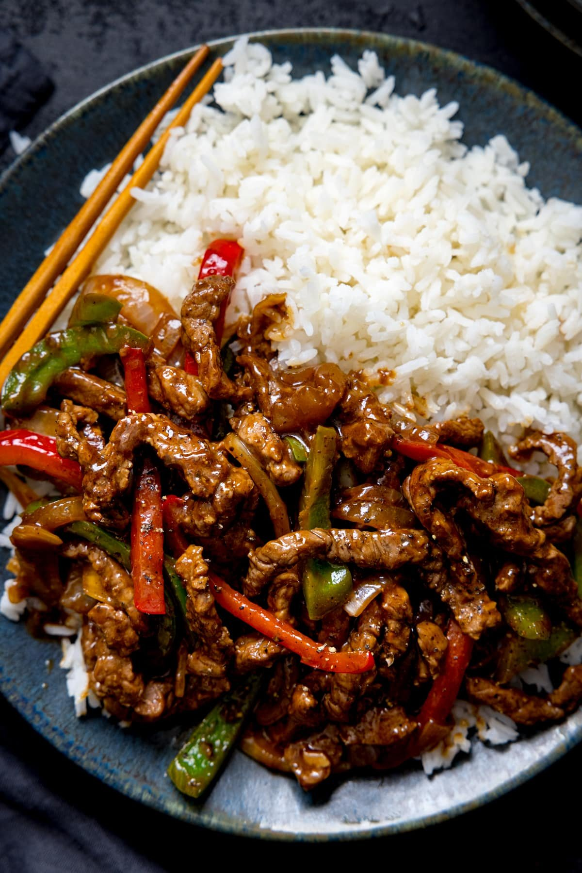 Black pepper beef stir fry with red and green peppers in a black bowl with boiled rice.