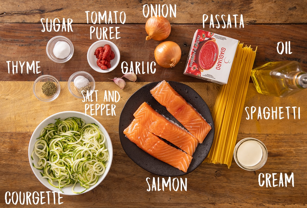 Ingredients for creamy tomato salmon and pasta on a wooden table