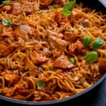 Spaghetti and pieces of salmon on a creamy tomato sauce in a pan