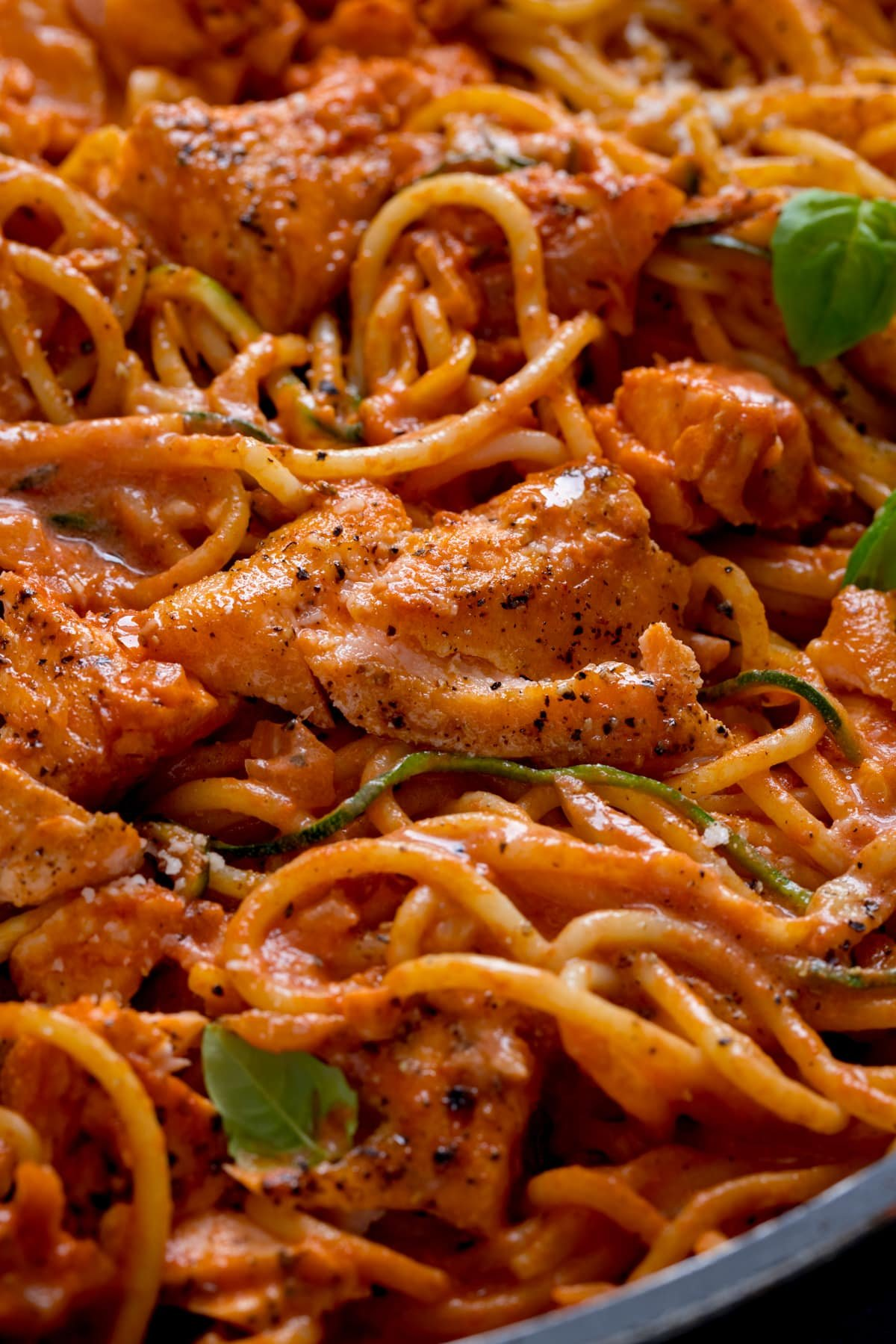 Close up of pieces of seasoned salmon in spaghetti in a creamy tomato sauce.