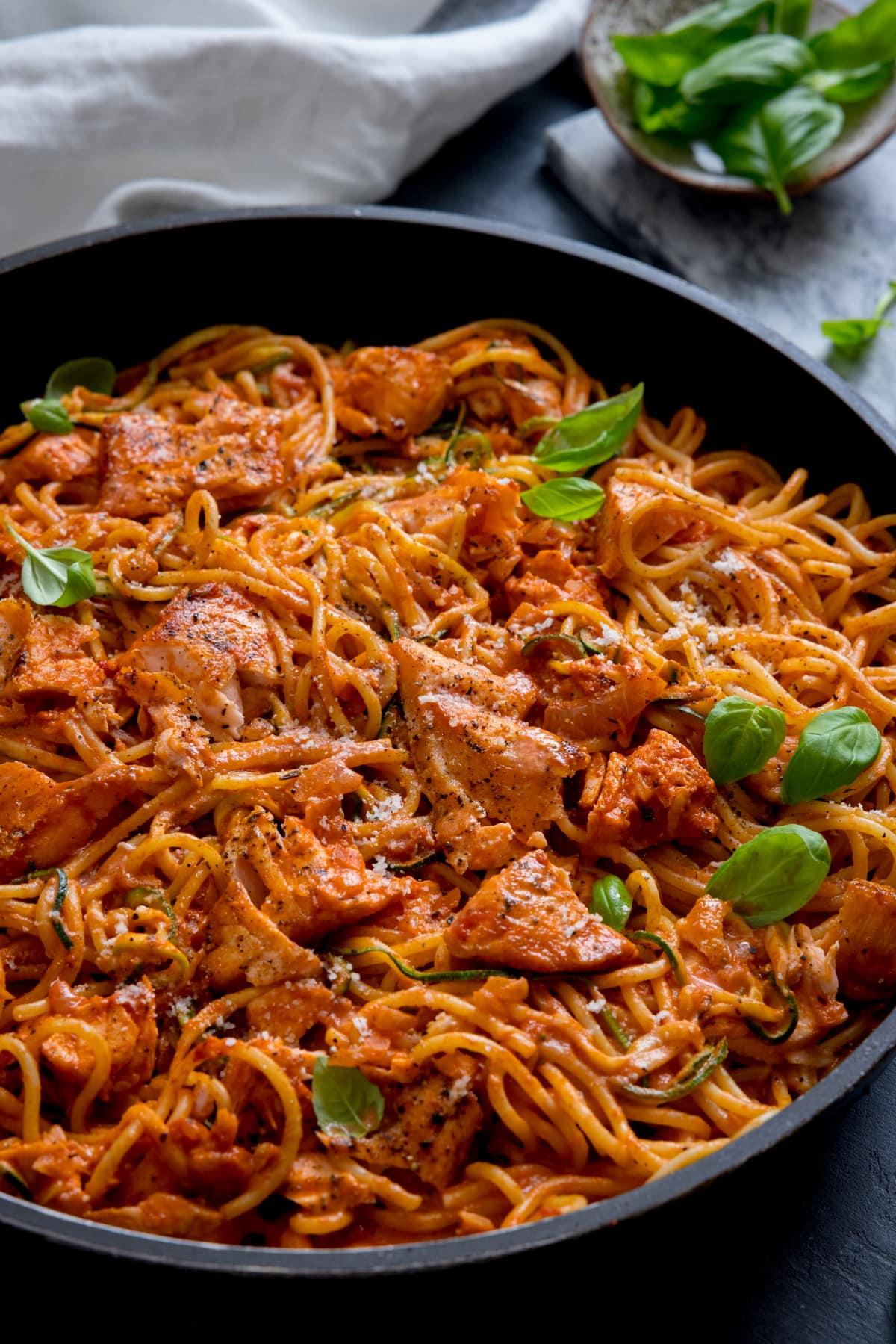 Creamy tomato spaghetti and salmon in a dark pan.