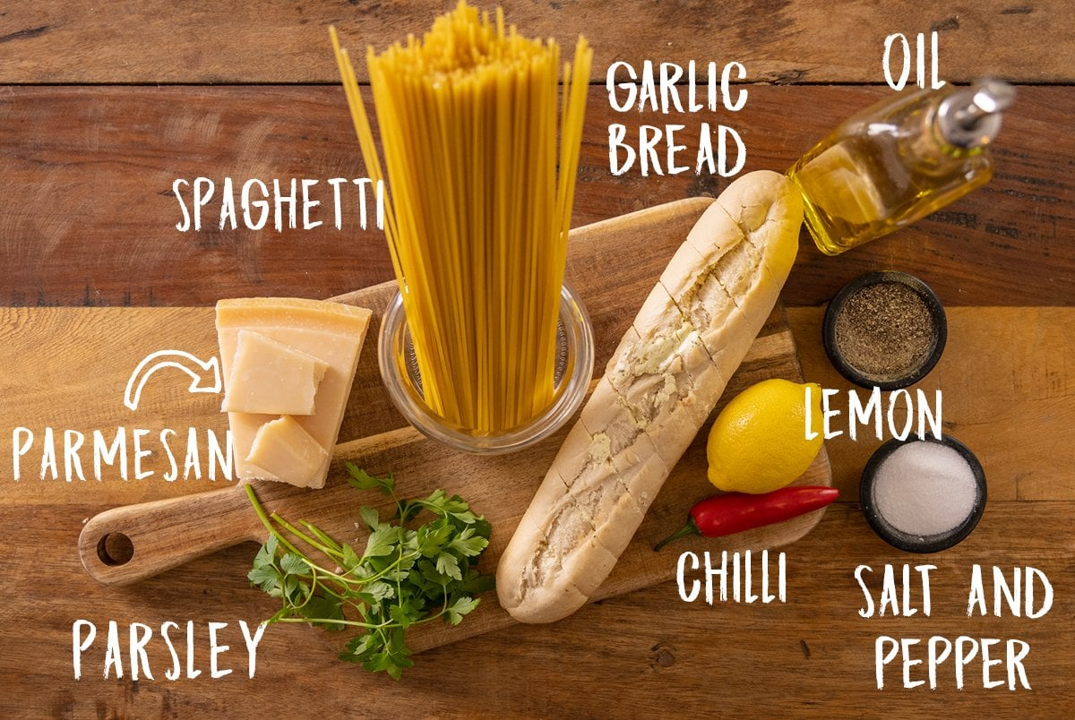 Ingredients for garlic bread spaghetti on a wooden table