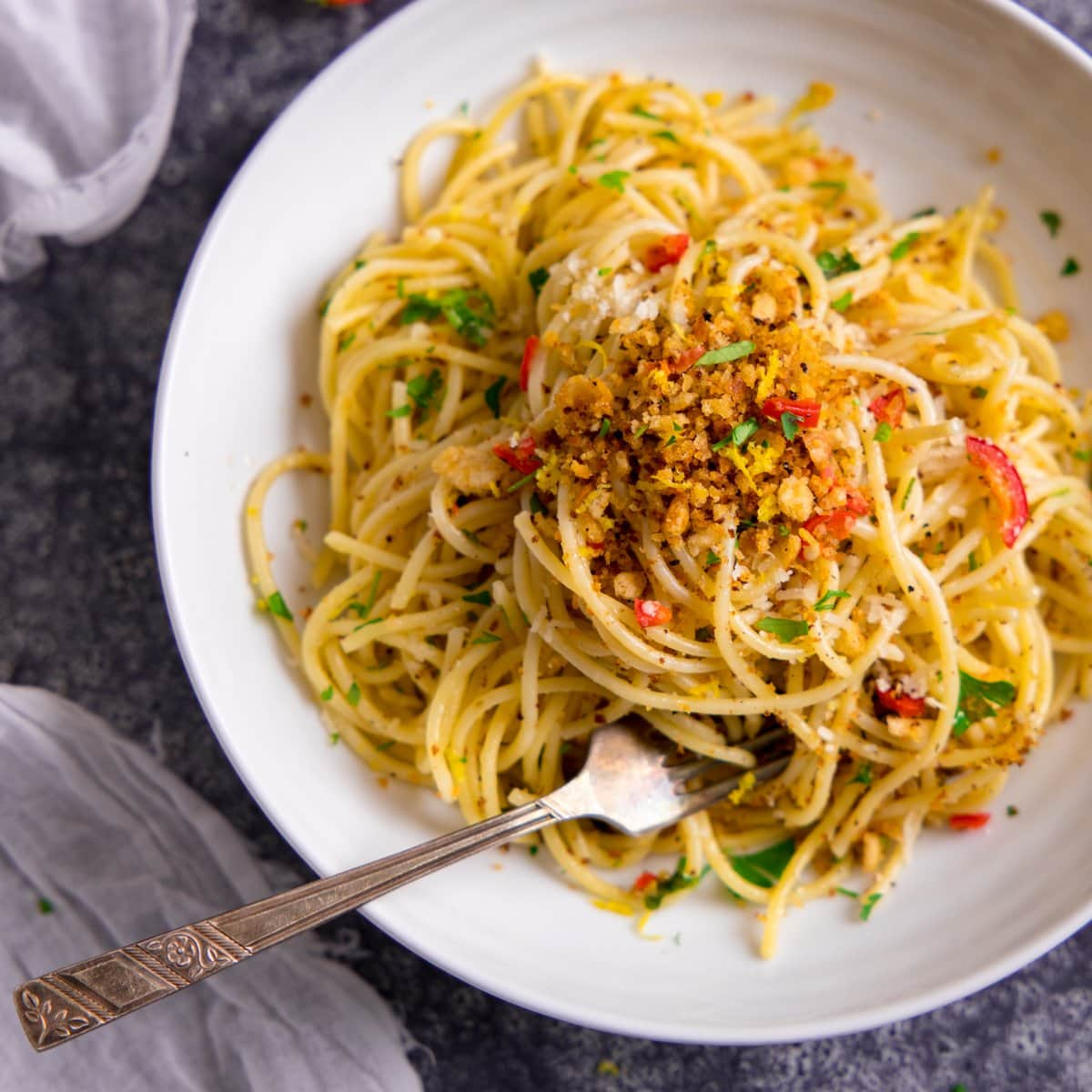 Spaghetti with garlic breadcrumbs and red chilli on a white plate.