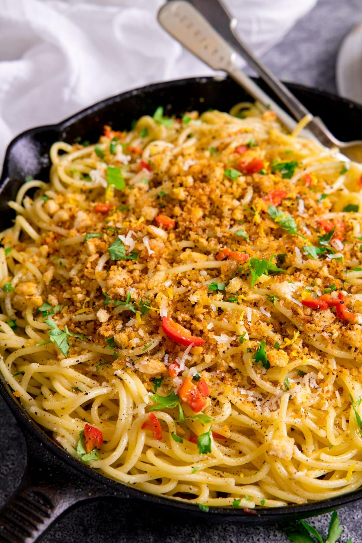 Black pan filled with spaghetti this is mixed with garlic breadcrumbs, chilli and parmesan.