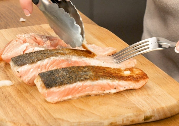 Two partially cooked salmon fillets on a board - skin being removed using a fork and a set of tongs