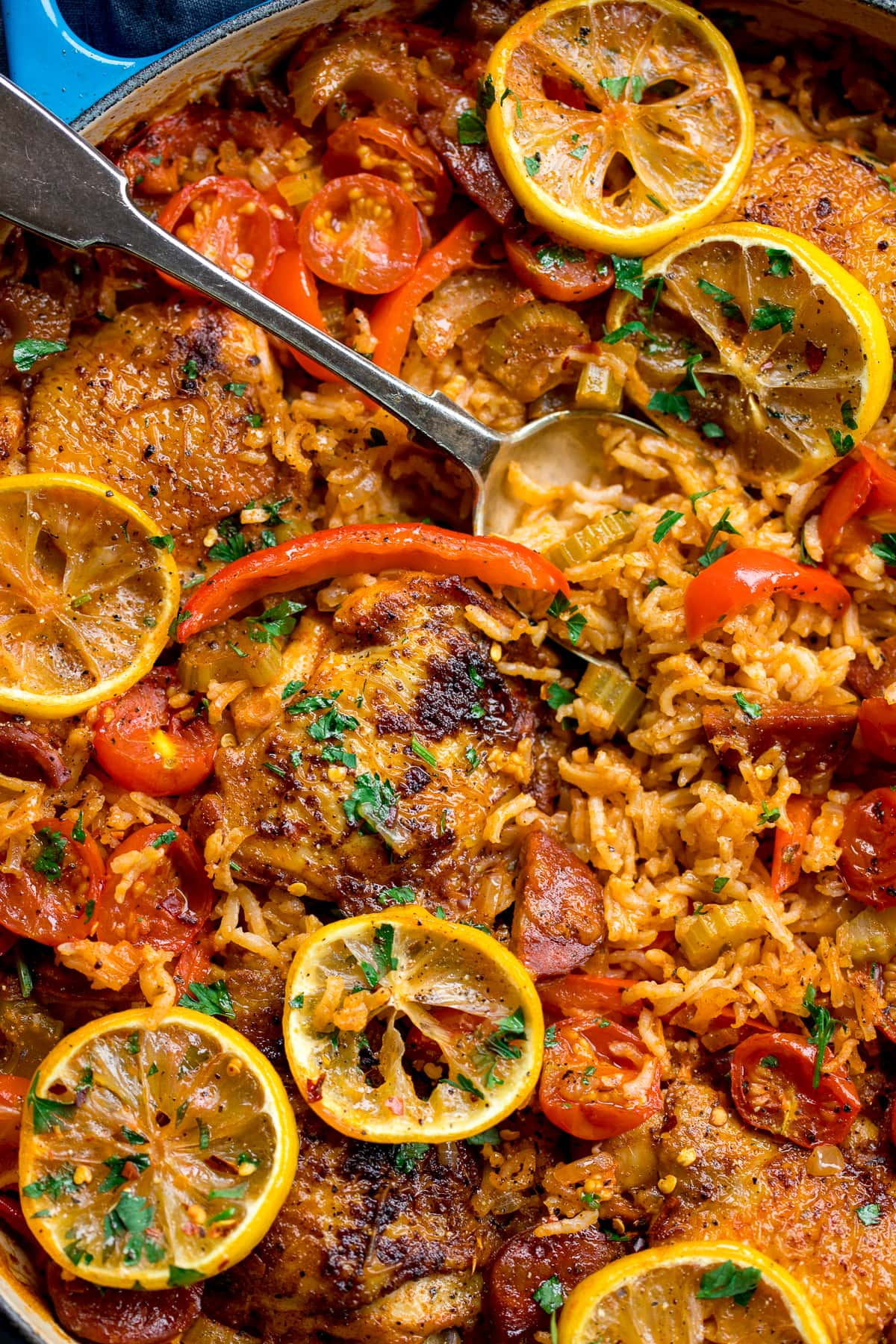 Overhead of Spanish chicken and rice with lemon slices, tomato and red peppers in a blue pan