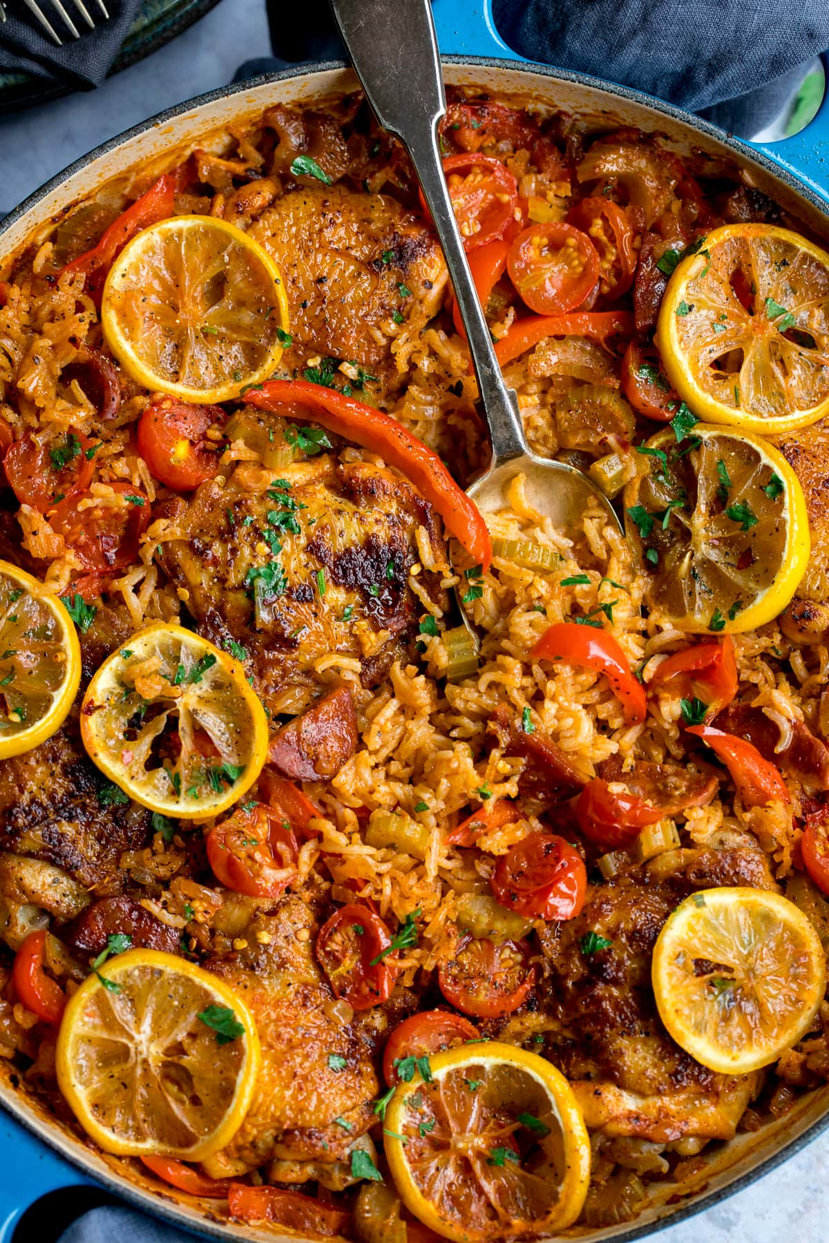 Blue pan filled with Spanish chicken and rice, topped with sliced lemons