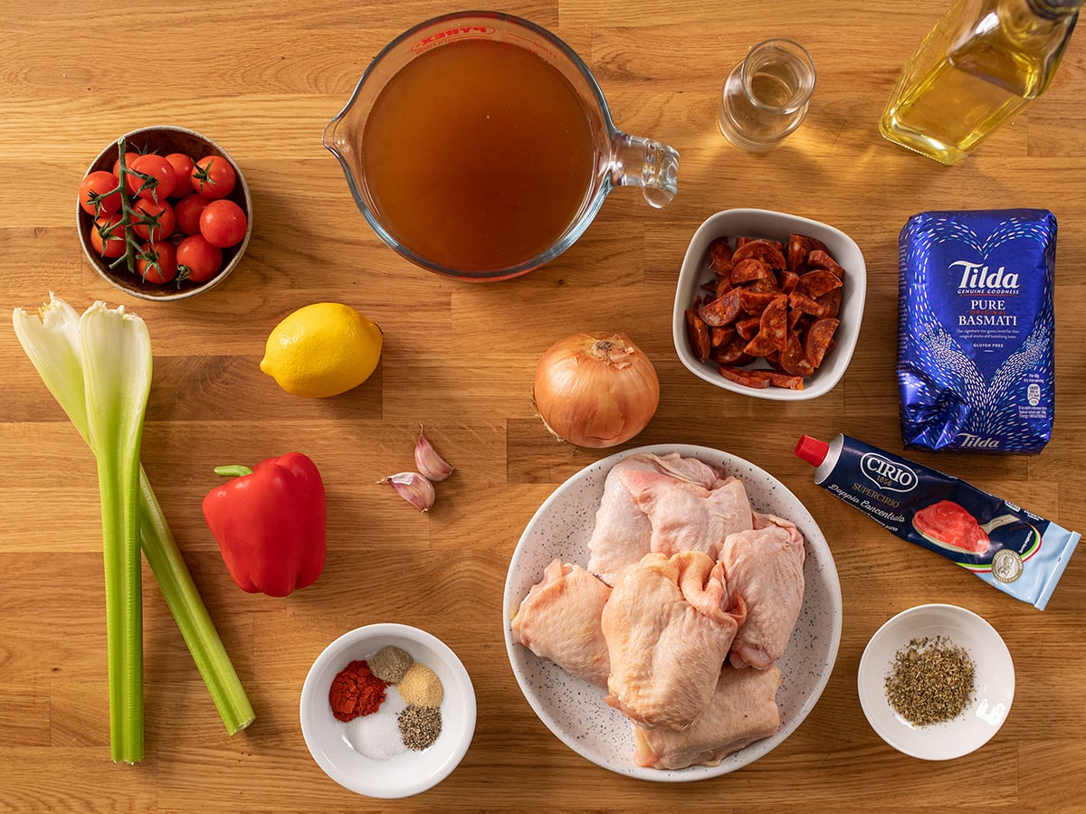 Ingredients for Spanish chicken and rice on a wooden table