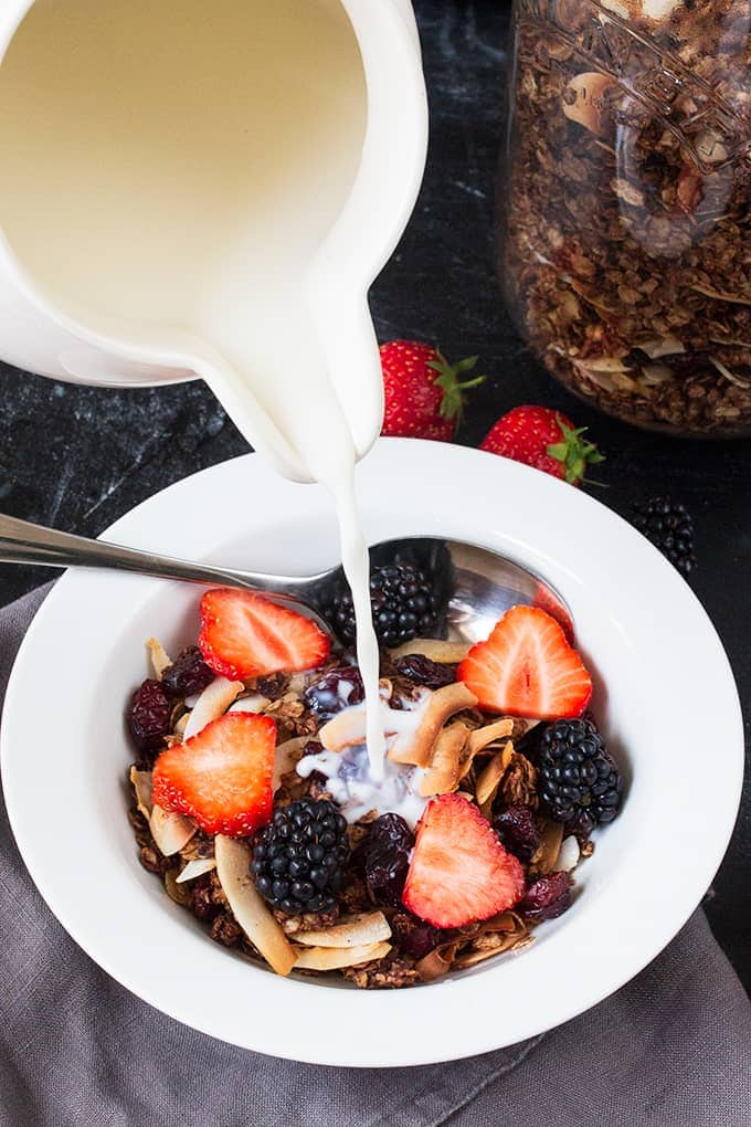 Pouring milk onto a bowl of chocolate coconut granola with cranberries with strawberries