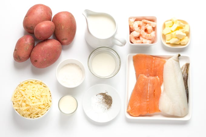 Ingredients for fish pie on a white board