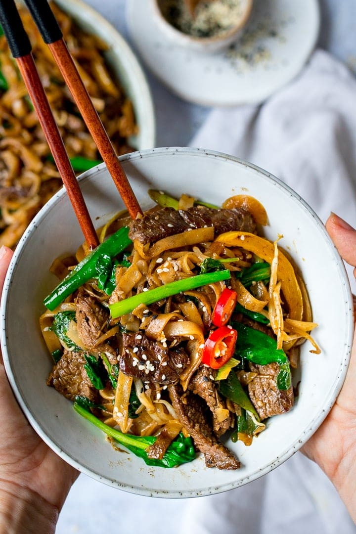 Hands holding bowl of Beef Chow Fun with chopsticks