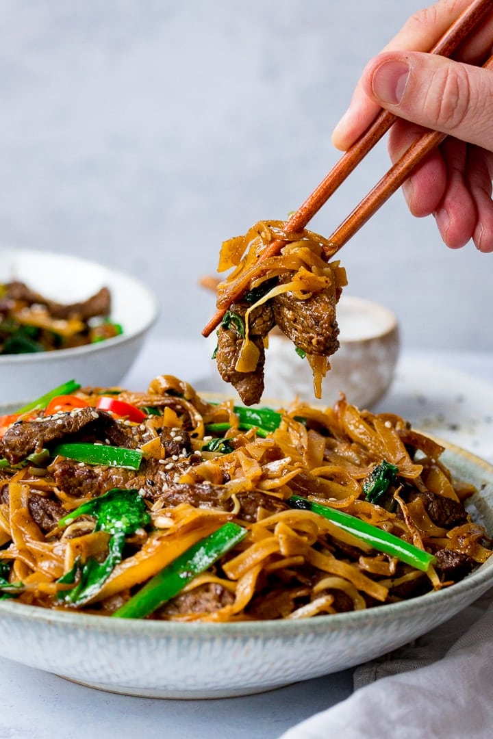Beef Chow Fun being taken from a bowl with chopsticks