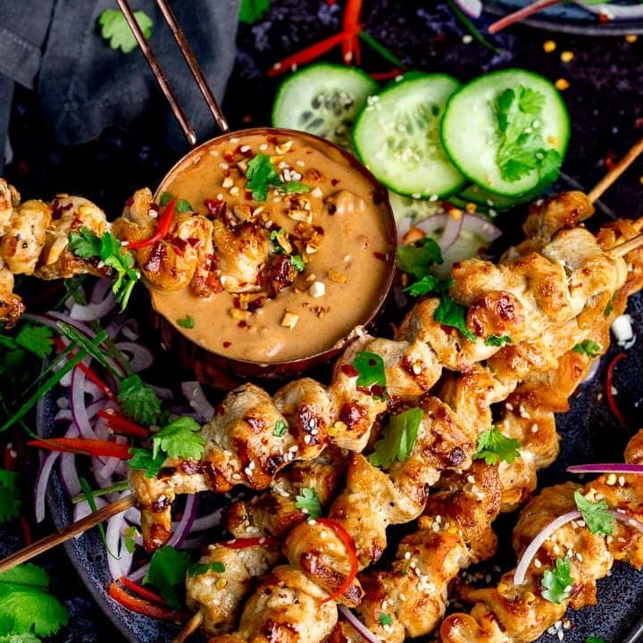 Square image of Chicken skewers with peanut satay sauce on a dark background
