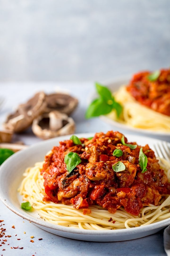 Plate of spaghetti topped with chicken and red pepper sauce on a light background