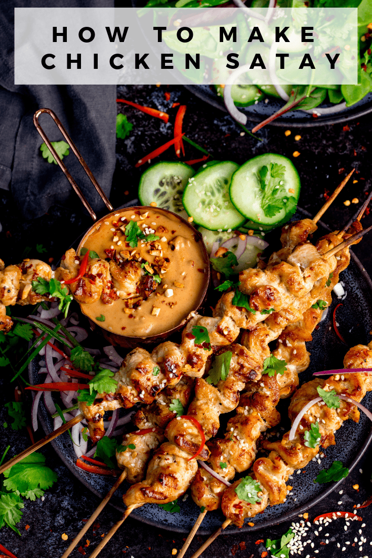 Chicken skewers with peanut satay sauce on a dark background