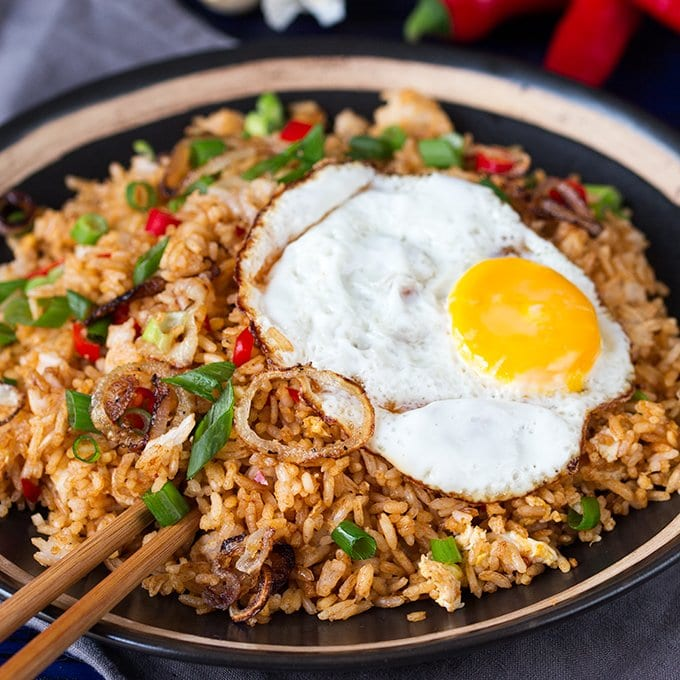 Bowl of spicy Indonesian fried rice with an egg and some chopsticks