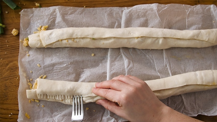 Sealing the pastry seams with a fork for vegetarian sausage rolls