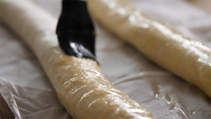 Brushing vegetarian sausage roll with egg wash before placing in oven.