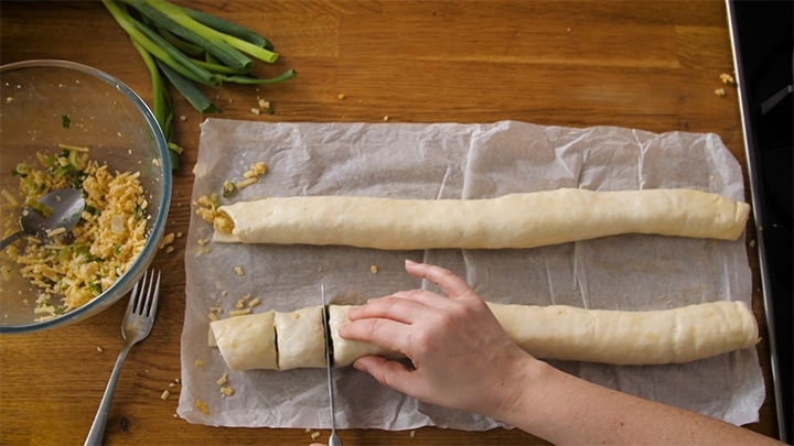 Slicing vegetarian sausage rolls into small sausage rolls before placing in oven.