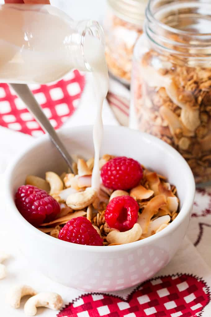 White Chocolate Coconut Cashew Granola in a white bowl with milk being poured over from a bottle