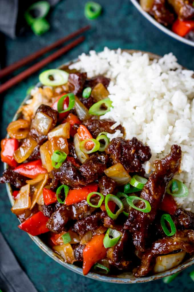 Overhead shot of crispy orange beef with onions and peppers in a bowl with rice