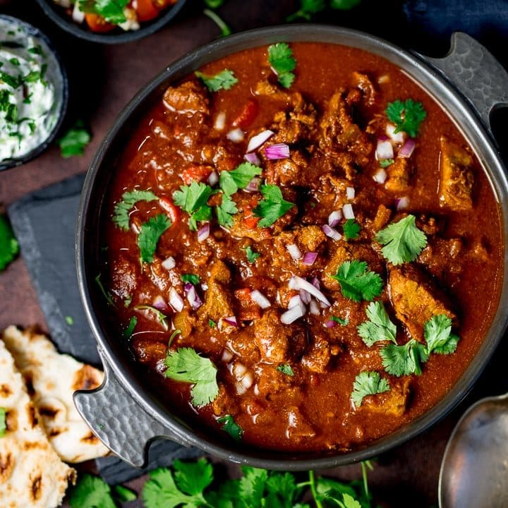 Slow-cooked spicy beef curry in a dish on a dark background