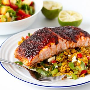 Spiced caramelised salmon served on a bed of savoury rice with feta and veggies. Colourful, healthy and delicious!