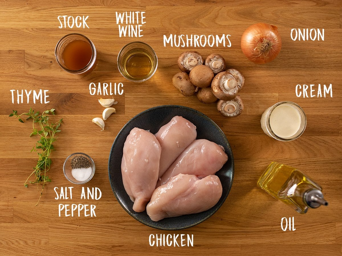 Ingredients for chicken in creamy white wine sauce on a wooden table
