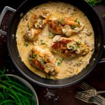 chicken in creamy white wine sauce in a dark pan next to a bowl of green beans