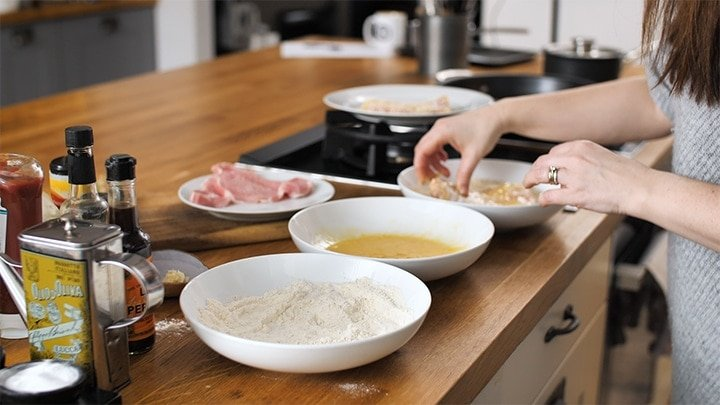 Pork cutlets being dredged through flour, egg and breadcrumbs