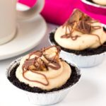 Mini Snickers Cheesecakes - with an Oreo base, peanut butter cheesecake and Snickers pieces. Totally addictive!