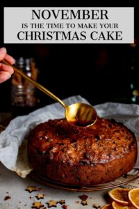 Cherry brandy being spooned onto fruit Christmas cake. Text overlay on the image.