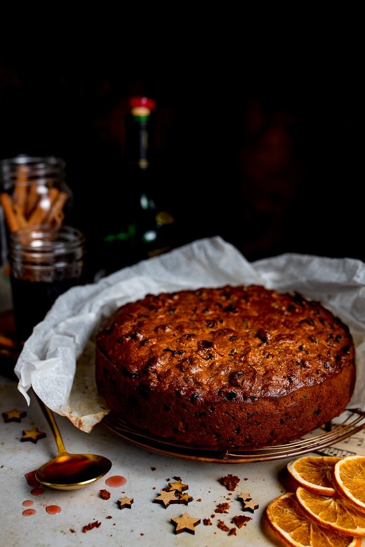 A fruit cake sat on a cooling rack with a spoon of cherry brandy to one side and some festive Christmas decorations in the foreground.