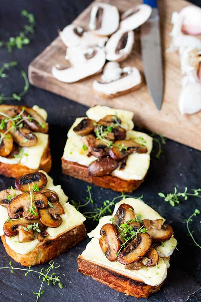 Garlic Mushroom and Brie Toast cut into squares with a sprig of thyme ontop