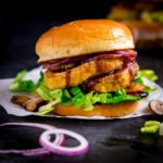 halloumi burger with lettuce and onions on a piece of parchment paper on a dark background