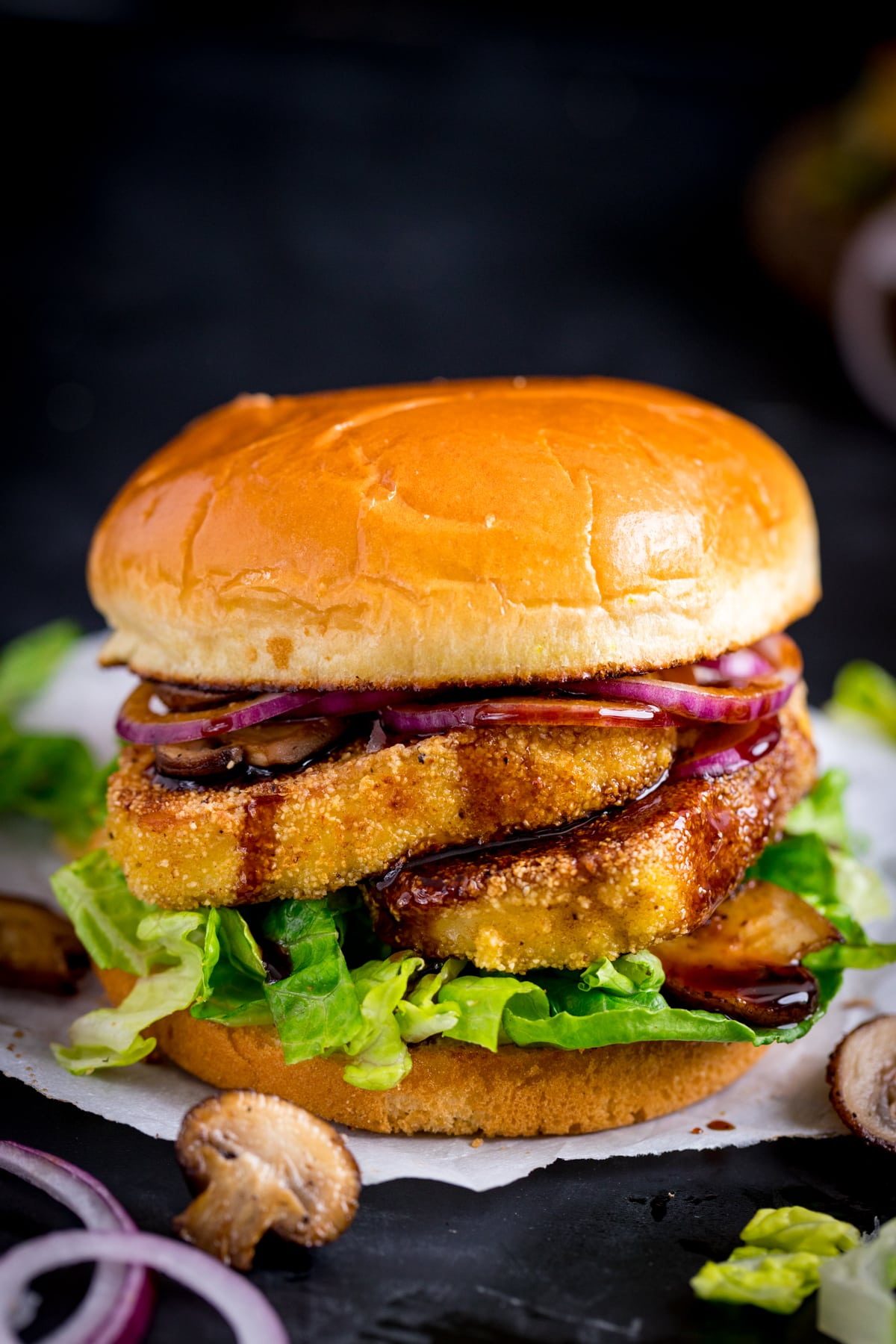 halloumi burger with lettuce, onions and mushrooms against a dark background.