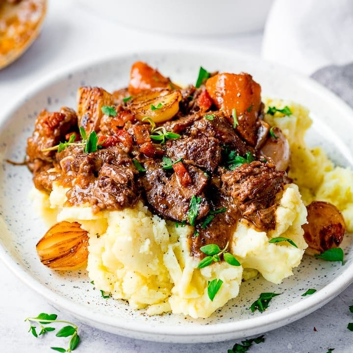 Beef bourguignon on top of mashed potato on a white plate