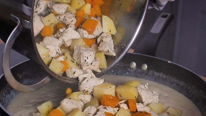 Adding chicken and vegetables to creamy sauce for pie filling