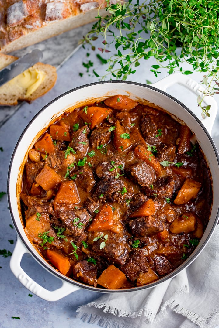 Large white pan filled with Scottish beef stew on a light background. Bread and fresh herbs also in scene.