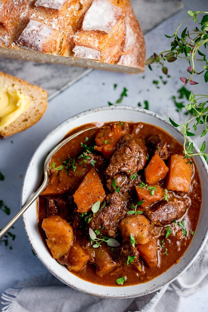 Bowl of Scottish beef stew with a spoon in it. Bread in the background.