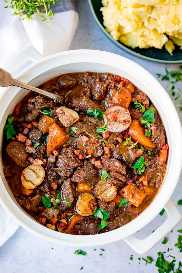 Overhead image of beef bourguignon in a pan on a light background